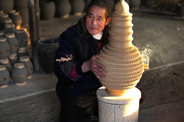 湖南省邵阳市洞口县高沙镇瓦罐已有一千多年的历史,先前的瓦罐有仙鸡窑、冷水窑等20多家,鼎盛时期有工匠500多人,目前工匠才十几人,手工技术正面临消亡。      制瓦罐所选取的黄土应是黄中带白,这种黄土粘性好,烧制出来的瓦罐才不会裂开,制作瓦罐的过程简单却又富有情趣。其中烧制是最重要的一个程序,用柴烧制,需要1200的高温,烧制的唯一秘诀就是凭经验用肉眼看。   现在有些手工制陶已被时尚的瓷器、木器、塑料制品所代替,村里制作瓦罐的人越来越少,但是向师傅在父亲的要求下坚持下来。生产的陶器随着时代的变迁融入那
