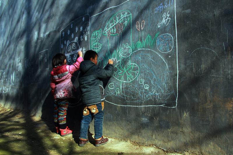 兩個孩子在房屋外墻上用彩色的粉筆畫畫,用童真描繪著他(她)們童年的